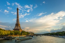 Beautiful sunset over Eiffel Tower and Seine river with puffy clouds, Paris, France