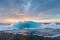Beautiful sunset over famous Diamond beach, Iceland. This sand lava beach is full of many giant ice gems, placed near glacier lagoon Jokulsarlon Ice rock with black sand beach in southeast Iceland