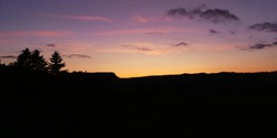 Beautiful sunset over French mountains on a summer evening. Black silhouettes of rocks and spruce trees silhouetted against the purple sky. The beauty of nature. Panoramic format
