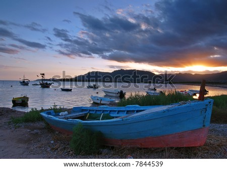 Beautiful sunset over harbor with a ship detail with dramatic sky on Sardinia