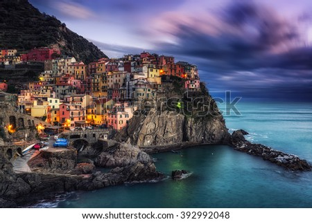 beautiful sunset over manarola in cinque terre, Italy. Sunlight lighting up the tips of the stormy clouds just before the night dawned. Manarola is a small coastal town in cinque terre, Italy.