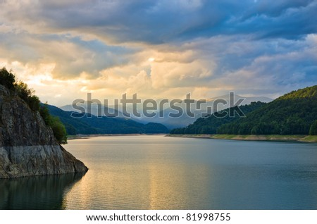 beautiful sunset over mountain lake with cloudy sky - stock photo