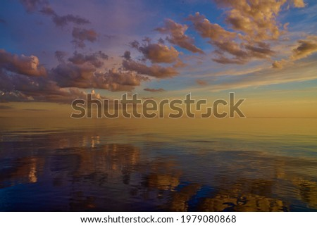 Beautiful sunset over sea with reflection in water, majestic clouds in the sky. ストックフォト ©