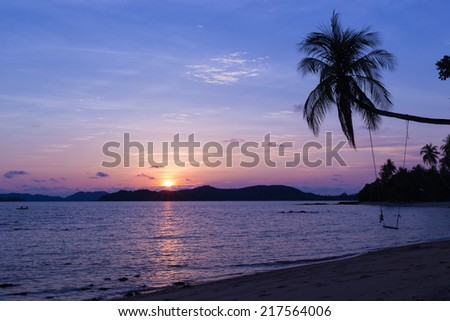 Beautiful sunset over the beach with coconut palm tree and hanging seat - Mak island,Thailand