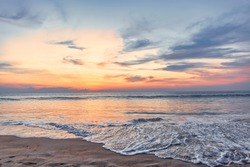 Beautiful sunset over the clam sea with cloud and sky background. Sunset over tropical beach. Nature summer  concept. Peak sunset over sea with yellow light reflect in cloud. soft focus