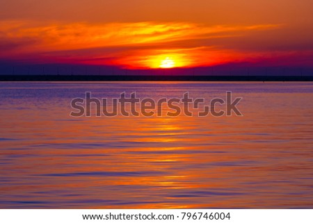 Beautiful sunset over the sea, crimson waves against the background of a red colorful dramatic cloudy sky, scenic landscape. Coastal seascape on the Black Sea, Sochi, Russia. #796746004