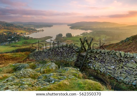 Beautiful sunset over Windermere in the Lake District with a stile and stone wall in the foreground.