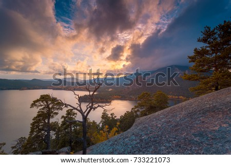 Beautiful sunset. Pine trees at sunset on a rocky mountains hill against dramatic clouds. Mountain lake on background. #733221073