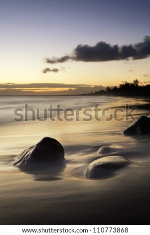 Beautiful sunset reflected in sandy coastline with stones in the foreground.