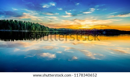 Beautiful sunset reflected in the lake. Clouds reflecting on the water. #1178340652