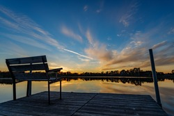 Beautiful sunset reflecting on the water at the public boat landing and dock with bench on Little Moon Lake, Barron County WI