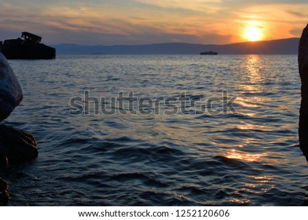 Beautiful Sunset Seen from Near a Partially Abandoned Shipyard on Olkhon Island, Lake Baikal, Russia. An Abandoned Ship Can Be Seen to the Left.