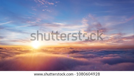 Beautiful sunset sky above clouds with dramatic light. Cabin view from airplane #1080604928