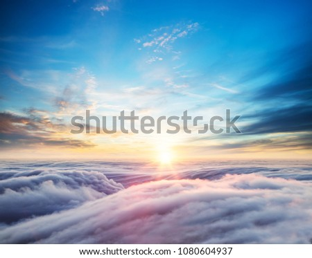 Beautiful sunset sky above clouds with dramatic light. Cabin view from airplane #1080604937