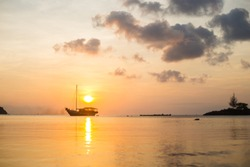 Beautiful sunset sky and fishing boat on the sea.