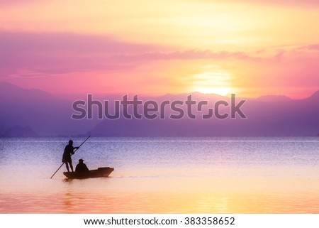Beautiful sunset sky and silhouettes of Minimal fisherman at the lake in pastel color. #383358652