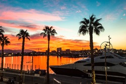 Beautiful sunset sky in the marina bay of Malaga city. Stunning orange seascape.