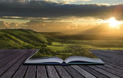 Beautiful sunset view across countryside spills out of magical book and creates stunning landscape background