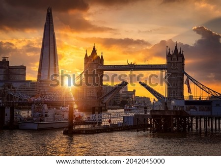 Beautiful sunset view to the Tower Bridge of London, United Kingdom, lifted up so ships can pass by on the Thames River Stok fotoğraf ©