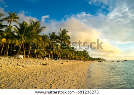 Beautiful sunset views of the beach on the island of Mauritius. Transparent ocean, white sand, palm trees on a background of mountains and clouds #681236275
