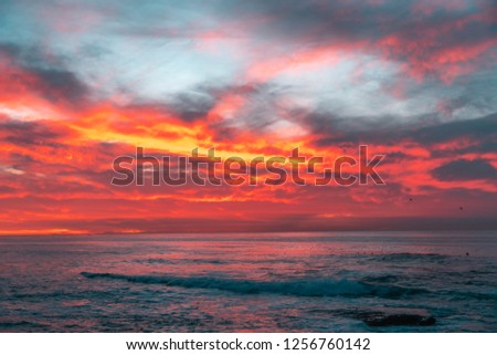 Beautiful sunset with clouds lit by sun on sea #1256760142