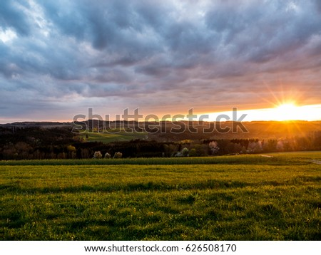 Beautiful sunset with dramatic cloudy sky and dandelions in rural Germany #626508170