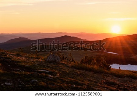 Beautiful sunset with rays over the contours of mountains with stones, small cedars and snow in the foreground #1125589001