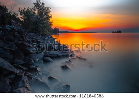 beautiful sunset with rock and smooth water