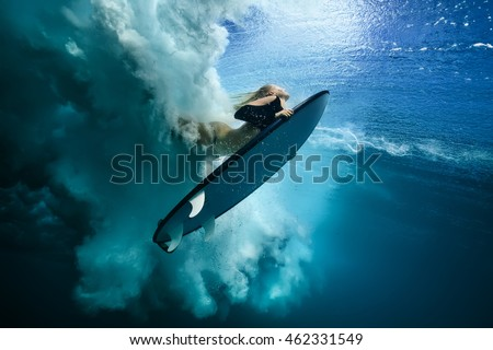 Stock Photo Beautiful Surfer Diving Duckdive under Big Ocean Wave. Turbulent air bubbles and tracks after sea wave crashing. Ripples at water surface with sky color.