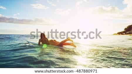 Beautiful surfer girl paddling into the sunset