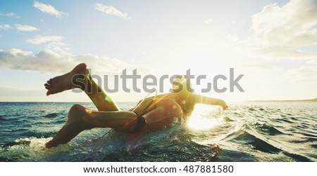 Stock Photo Beautiful surfer girl paddling into the sunset