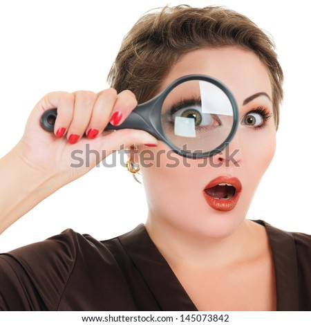 Beautiful surprised woman looking through a magnifying glass isolated over white background