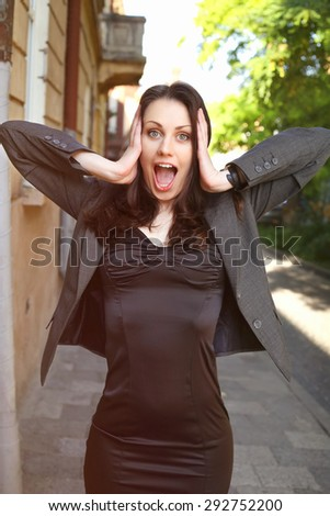 Beautiful surprised woman. Office worker. Office clerk in shock. The stress of the business world. Business fashion business style. Business woman on the street. Shock, surprise, stress.