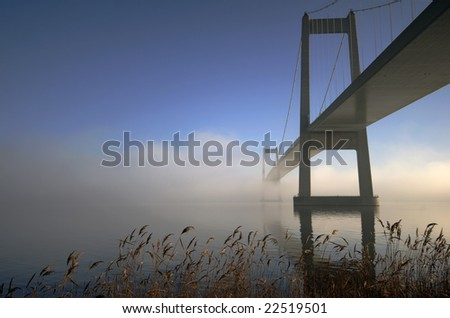Beautiful suspension bridge.  Blue and cold foggy day in Denmark - stock photo