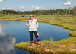 beautiful swamp landscape with blue sky and water, woman enjoys swamp landscape, hike with snowshoes in swamp, traditional swamp plants, mosses and trees, bog in summer