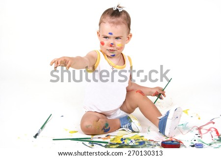 Beautiful, sweet and happy baby sitting on white background and draws paint. All smeared with colored background paint and spray