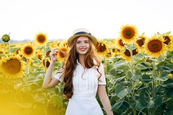 beautiful sweet sexy girl in a white dress walking on a field of sunflowers , smiling a beautiful smile,cheerful girl,style, lifestyle , ideal for advertising and photo sun shines bright and juicy