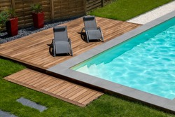 beautiful swimming pool and exotic wooden terrace with sunbath chair