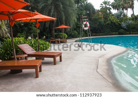 beautiful swimming pool surrounded by chairs and treess