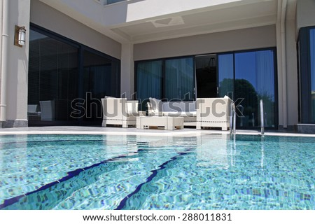 Beautiful swimming pool with white outdoor furniture on modern luxury resort