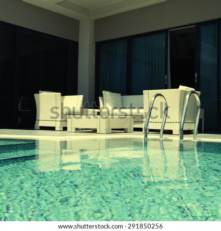 Beautiful swimming pool with white outdoor furniture on modern luxury resort, square toned image, instagram effect