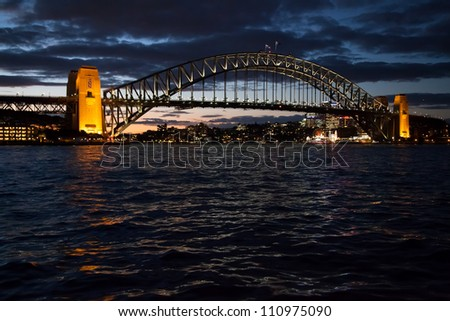 Beautiful Sydney Harbour Bridge at sunset with waves reflecting the light