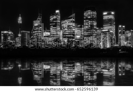 Beautiful Sydney Skyline at night in black and white of Central Business District seen from Farm Cove, with reflections in bay's water. #652596139