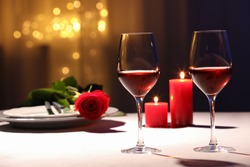 Beautiful table setting with glasses of wine, candles and rose against blurred lights. Romantic dinner for Valentine's day