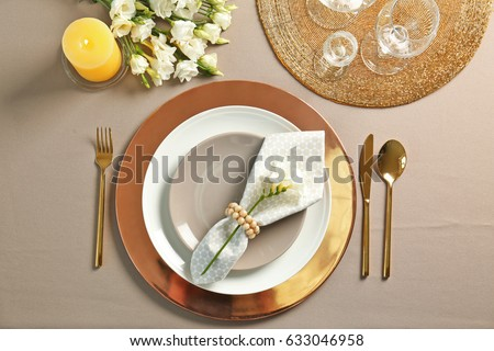 Beautiful table setting with golden flatware #633046958