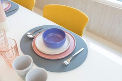 Beautiful table setting with pink and purple plate on table. Glassware and cutlery for catered event dinner.