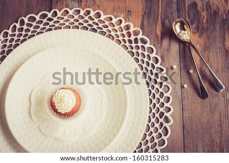 Beautiful tableware with little cupcake.  Selective focus on cupcake, top view. - stock photo