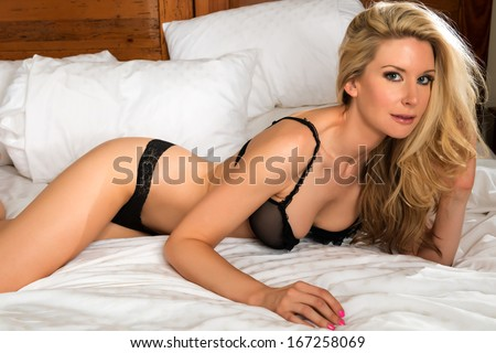 Beautiful tall blonde in bed in black lingerie