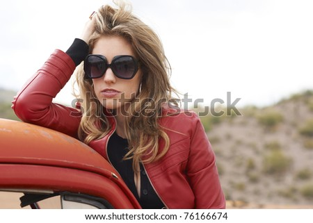 Beautiful tall fashion model wearing red leather jacket and sunglasses sitting on rustic vintage truck.