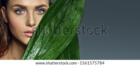 Beautiful tanned blue-eyed girl with natural make-up and wet hair holds wet exotic leaves near her face.Beauty, fashion, cosmetology, natural, nature, natural, spa, detox, plants.